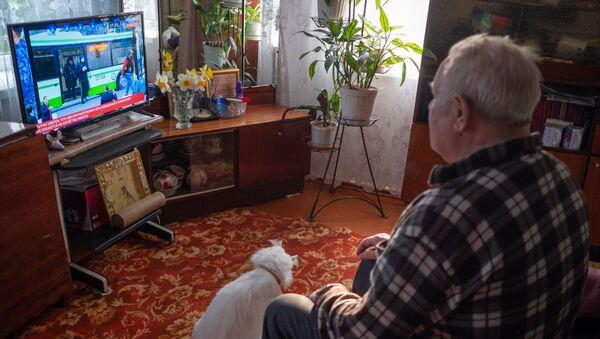 Čovek gleda televiziju kod kuće tokom samoizolacije zbog epidemije virusa korona u Krasnodarskom kraju Rusije - Sputnik Srbija