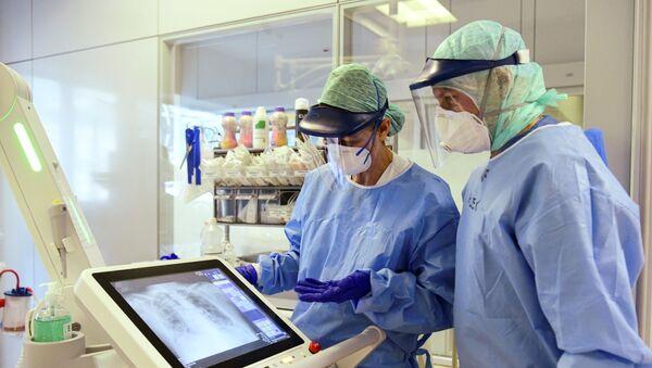 Запослени клинике у Бергаму у заштитним маскама гледају рендгенски снимак плућа пацијента који има вирус корона - Sputnik Србија