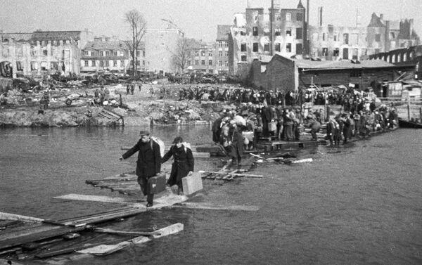 Становници Кенигсберга на привременим мостовима прелазе реку, враћајући се кући. - Sputnik Србија