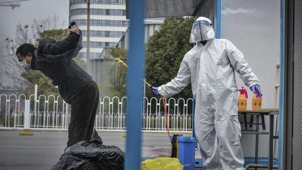 Dezinfekcija oporavljenog pacijenta pre otpusta iz bolnice u Vuhanu u Kini - Sputnik Srbija