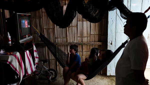 Ђина и њен супруг Виктор који последњих недеља нису могли да раде због мера које је држава предузела против вируса корона, са децом гледају ТВ у Еквадору. - Sputnik Србија