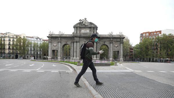 Човек са заштитном маском и рукавицама пролази поред пустог трга у Мадриду - Sputnik Србија