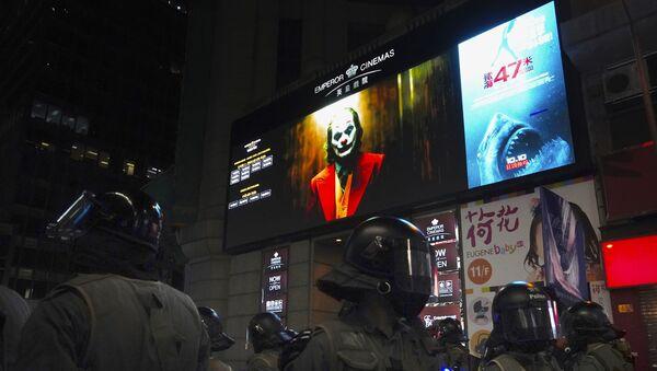 """Полицајци у Хонгконгу у опреми стоје у близини биоскопа где се приказује филм """"Џокер""""  - Sputnik Србија"""