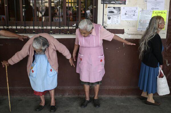 Starije žene održavaju udaljenost jedna od druge dok čekaju da se upišu u državne programe socijalne pomoći u centru Ozumba, u Meksiku, 3. aprila 2020. godine, za vreme izbijanja pandemije novog virusa korona.  - Sputnik Srbija