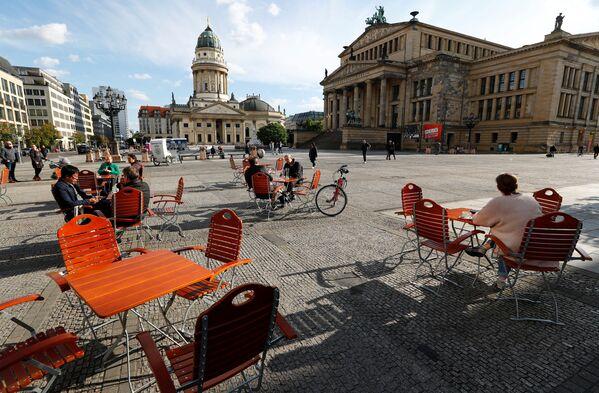Ljudi uživaju u lepom vremenu u kafiću na trgu Gendarmenmarkt, gde se primenjuju mere fizičkog distanciranja za vreme epidemije virusa korona, u Berlinu, Nemačka, 16. maja 2020. godine. - Sputnik Srbija