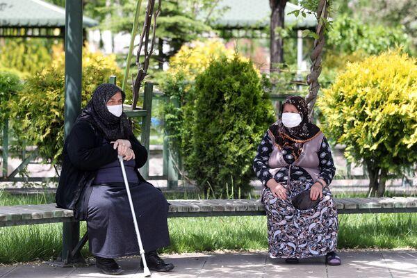 Starije žene, noseći zaštitne maske za lice, sede na klupi parka u okrugu Akijurt, jer je osobama starijim od 65 godina i pacijentima sa hroničnim bolestima širom Turske dozvoljeno da napuštaju svoje domove, poštuju određenu udaljenost i nose maske između 12 i 18 časova po lokalnom vremenu, u Ankari 17. maja 2020. godine. - Sputnik Srbija
