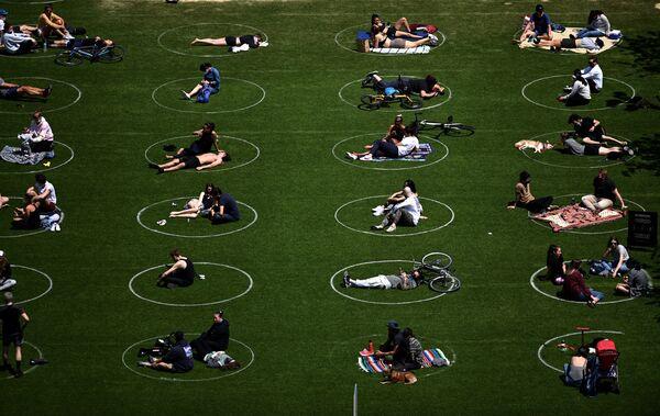 Ljudi praktikuju društveno distanciranje sedeći u označenim belim krugovima u Domino parku tokom pandemije kovida 19, 17. maja 2020. u Bruklinu u Njujorku. - Sputnik Srbija