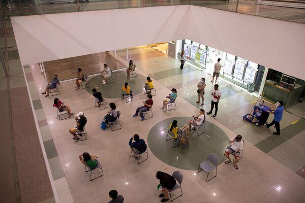 Kupci održavaju fizičku distancu dok čekaju da uđu u prodavnicu u tržnom centru, koja se ponovo otvara nakon dva meseca jer se ograničenja karantina olakšavaju usled izbijanja bpandemije, u gradu Kuezon, Metro Manila, Filipini, 17. maja 2020. - Sputnik Srbija