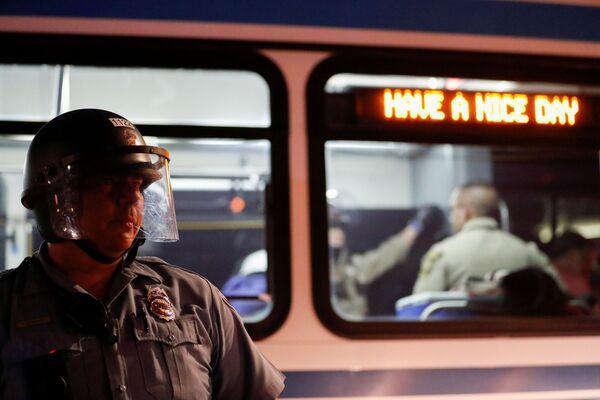 Полицајац стоји испред аутобуса током протеста усред немира у земљи након смрти Афроамериканца Џорџа Флојда у Минеаполису. - Sputnik Србија