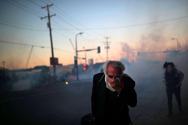 Човек усред нереда у коме су употребљени сузавци током протеста због смрти Џорџа Флојда у Минеаполису. - Sputnik Србија