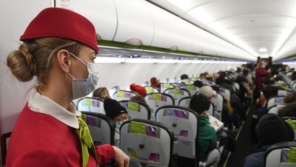 Стјуардеса са маском у авиону током лета - Sputnik Србија