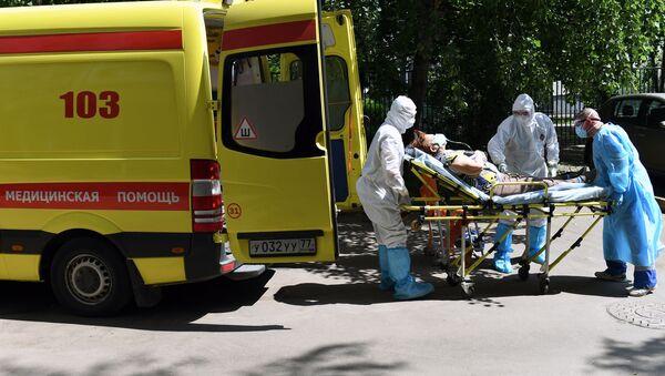Лекари хитне помоћи уносе  у возило пацијента са сумњом на вирус корона - Sputnik Србија
