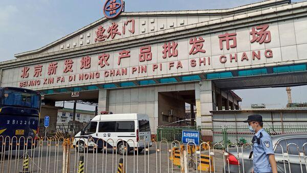 Полицајац са заштитном маском испред улаза у пијацу Синфади у Пекингу, која је затворена након избијања нове инфекције вируса корона - Sputnik Србија