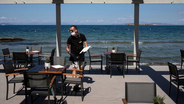 Radnik hotela u Grčkoj sa zaštitnom maskom na početku letnje sezone - Sputnik Srbija