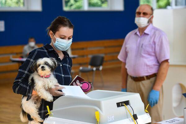 Devojka sa psom glasa na izborima o izmenama i dopunama Ustava Rusije na biračkom mestu u Moskvi. - Sputnik Srbija