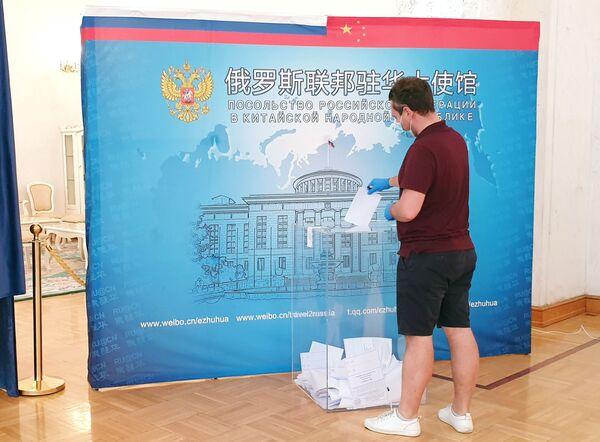 Muškarac glasa na biračkom mestu postavljenom u Ruskoj ambasadi u Pekingu u Kini.  - Sputnik Srbija