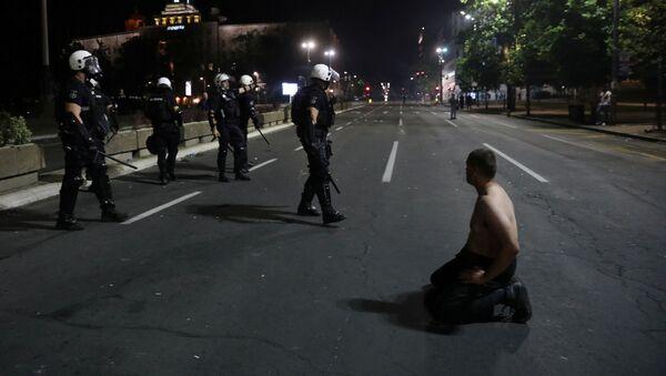 Демонстрант клечи испред припадника полиције на протесту испред Скупштине Србије у Београду - Sputnik Србија