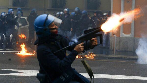 Policjac ispaljuje suzavac na proestima protiv EKSPO u Milanu , 1. maja 2015 - Sputnik Srbija