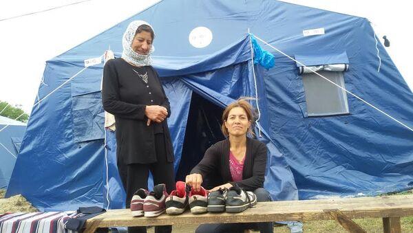 Сиријка Надиа и мајка њеног мужа проверавају да ли је обућа сува, од чега зависи полазак на даље путовање ка северу - Sputnik Србија