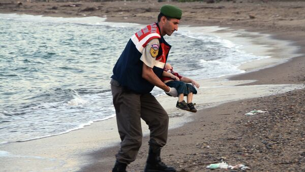 Турски полицајац носи тело трогодишњег дечака, избеглице из Сирије Ајлана Курдија - Sputnik Србија