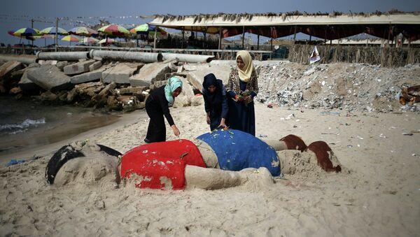 Mlade Palestinke na plaži u Gazi položile cveće na peščanu skulputuru sirijskog dečaka Ajlana Kurdija, trogodišnjeg dečaka koji se utopio u Turskoj u izbegličkom zbegu - Sputnik Srbija