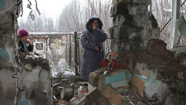 Donbas - lokalni stanovnici stoje ispred ruševina. - Sputnik Srbija