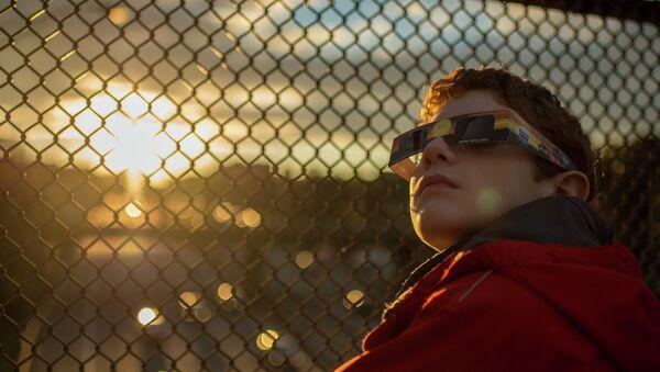 Dečak se sprema za posmatranje pomračenja sunca - Sputnik Srbija